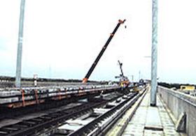 大型クレーンによるスラブ版の運搬トロへの積載状況
